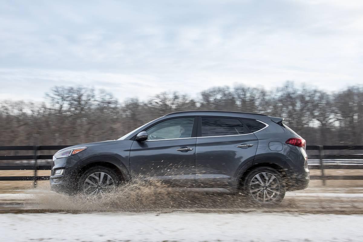 Gray 2019 Hyundai Tucson driving through a puddle