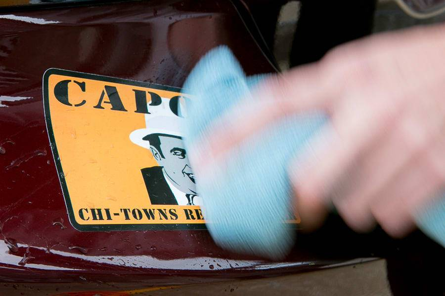 Wiping away dirt around the sticker on a car