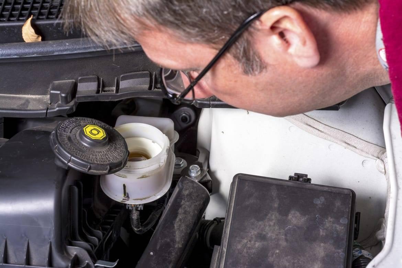 Brake fluid reservoir being inspected