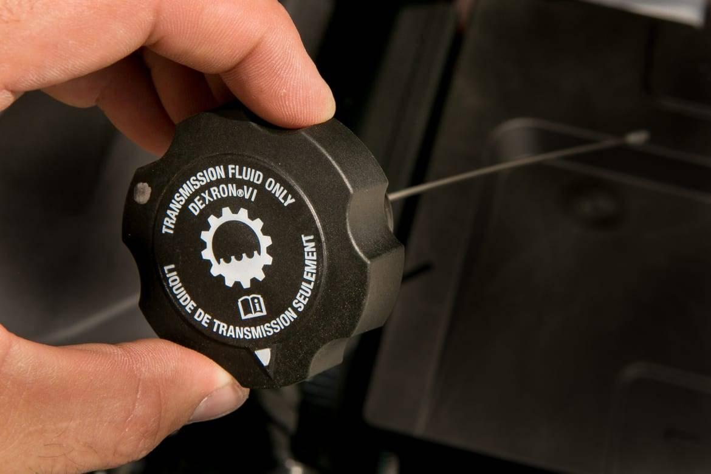 Transmission fluid reservoir cap being removed