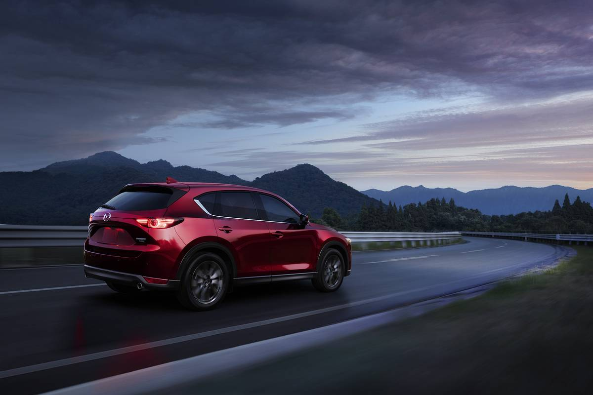 A red 2021 Mazda CX-5 driving down a road with mountains in the background