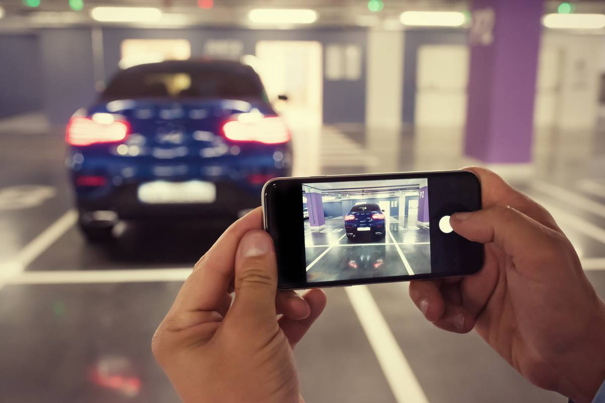 Person using a smartphone to take a picture of a car.