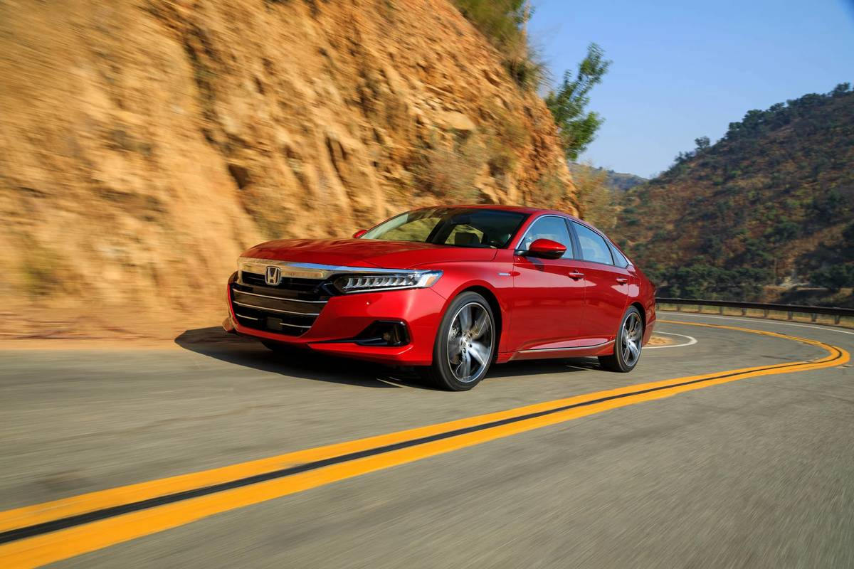 Red 2021 Honda Accord Hybrid driving on a winding road