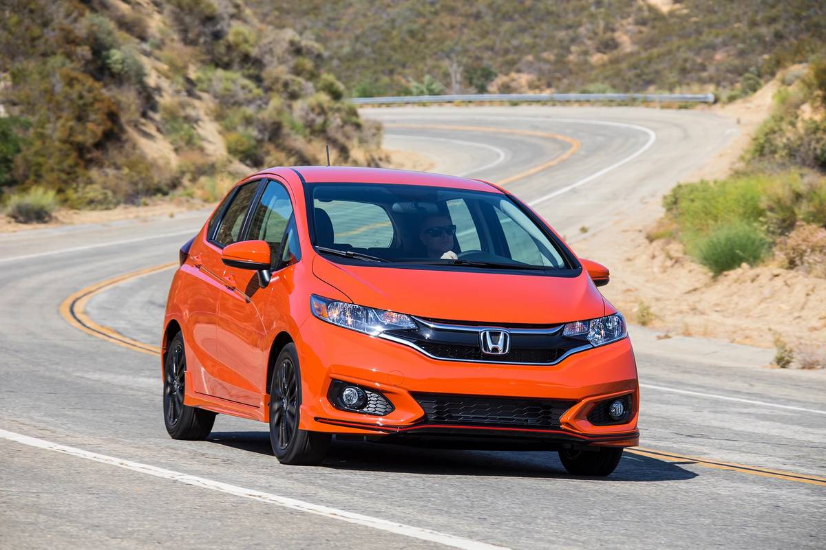Orange 2020 Honda Fit driving on a road
