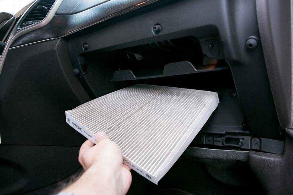 A cabin air filter being replaced on the passenger side of a car under the glove compartment