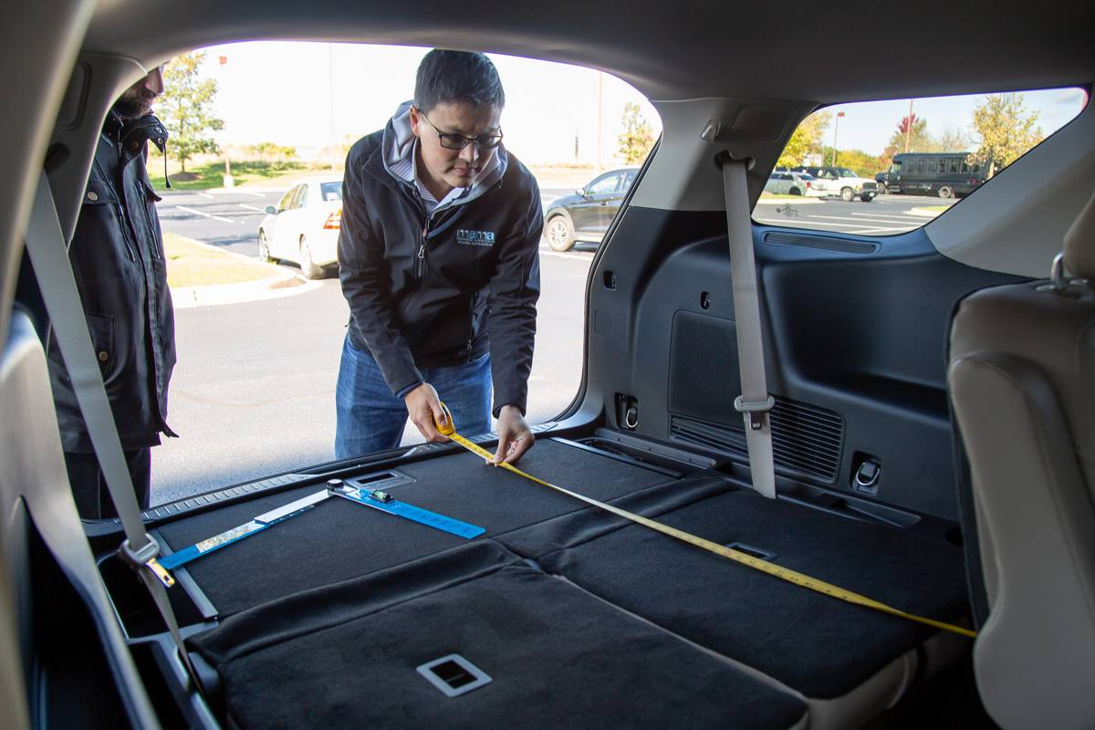 Person measuring the cargo space dimensions of an SUV