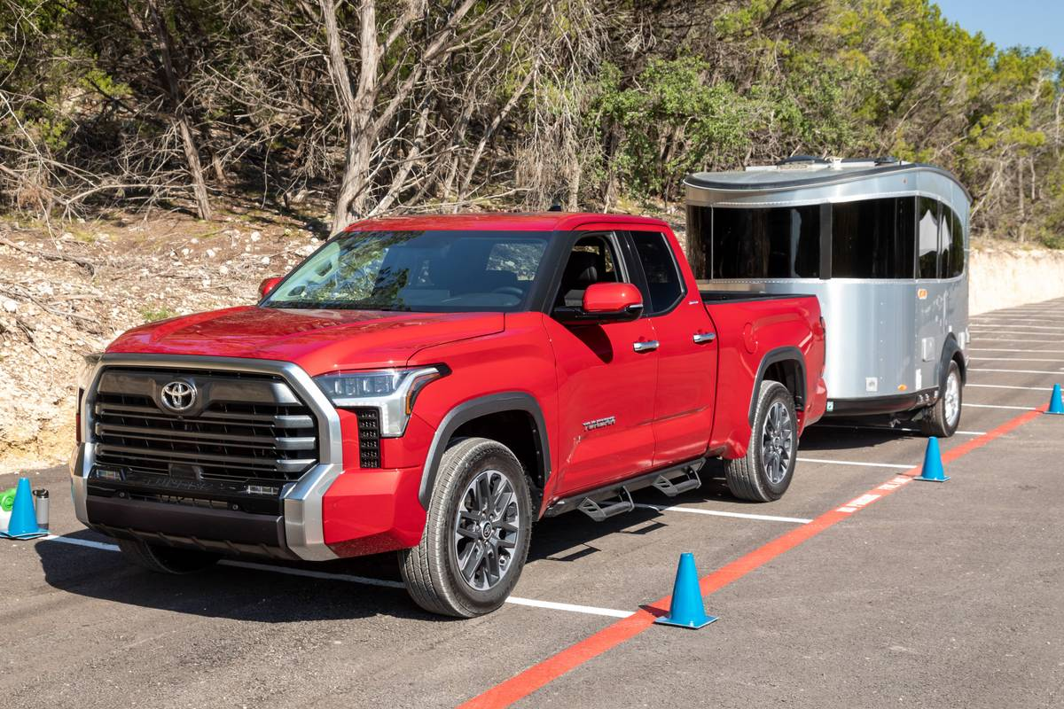 toyota-tundra-2022-02-towing-exterior-front-angle-mobile-trailer-red-truck
